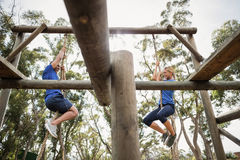 Fit man and woman climbing rope during obstacle course. Fit men and women climbing rope during obstacle course in boot camp stock photo
