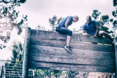 Fit man and woman climbing on wooden wall during obstacle course. In boot camp stock photography