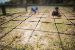 Fit man and woman crawling under the net during obstacle course. Fit men and women crawling under the net during obstacle course in boot camp stock photos