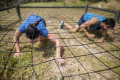 Fit man and woman crawling under the net during obstacle course. Fit men and women crawling under the net during obstacle course in boot camp stock images