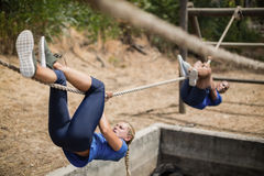 Fit man and woman crossing the rope during obstacle course. Fit men and women crossing the rope during obstacle course in boot camp stock image