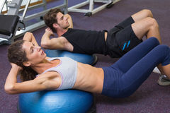 Fit man and woman doing sit ups on exercise ball. Fit men and women doing sit ups on exercise ball at the gym royalty free stock photos