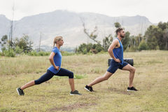 Fit man and woman exercising in boot camp. Fit men and women exercising in boot camp on a sunny day royalty free stock images