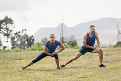 Fit man and woman exercising in boot camp stock image