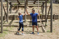 Fit man and woman giving high-five to each other during obstacle course stock images