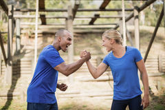 Fit man and woman greeting each other during obstacle course. Fit men and women greeting each other during obstacle course in boot camp royalty free stock image