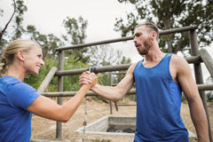 Fit man and woman greetings during obstacle course. Fit men and women greetings during obstacle course at boot camp stock images