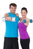Fit man and woman lifting dumbbells. Fit men and women lifting dumbbells on white background stock photos
