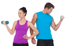 Fit man and woman lifting dumbbells Stock Photos