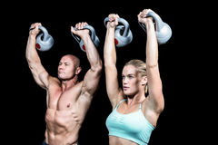 Fit man and woman lifting kettlebells. Fit men and women lifting kettlebells against black background royalty free stock photo