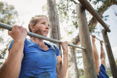 Fit man and woman performing pull-ups on bar during obstacle course. Fit men and women performing pull-ups on bar during obstacle course in boot camp royalty free stock photos