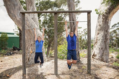 Fit man and woman performing pull-ups on bar during obstacle course Stock Image