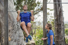 Fit man and woman performing pull-ups on bar during obstacle course Royalty Free Stock Photo