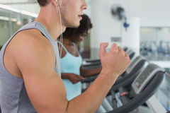 Fit man and woman running on treadmill. Fit men and women running on treadmill at the gym stock photo