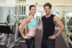 Fit man and woman smiling at camera together. Fit men and women smiling at camera together at the gym stock photo