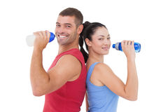 Fit man and woman smiling at camera together. Fit men and women smiling at camera together on white background royalty free stock photo
