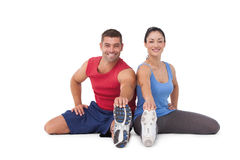Fit man and woman stretching legs. Fit men and women stretching legs on white background royalty free stock images