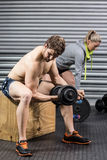 Fit man and woman working out. Fit men and women working out at crossfit gym royalty free stock photos