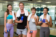 Fit man and women smiling at camera in studio Stock Images