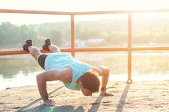 Fit man working out doing push-ups exercising outdoors Stock Photo