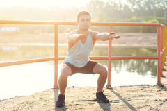 Fit man working out glutes with bodyweight workout doing squat exercises. Stock Images