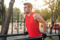 Fit man workout out arms on dips horizontal bars training triceps and biceps doing push ups outdoors. Stock Image