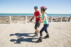 Fit mature couple rollerblading on the pier Stock Photos