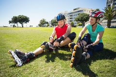 Fit mature couple tying up their roller blades on the grass Stock Photo
