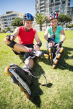Fit mature couple tying up their roller blades on the grass Royalty Free Stock Photos