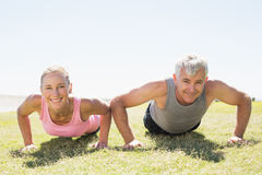 Fit mature couple warming up on the grass Royalty Free Stock Photos