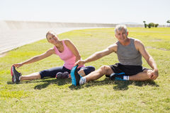 Fit mature couple warming up on the grass Stock Images
