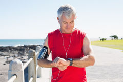 Fit mature man checking the time on the pier Stock Photo