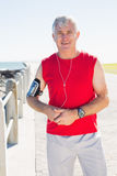 Fit mature man smiling at camera on the pier Royalty Free Stock Image