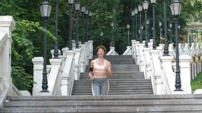 Fit mature female running down the stairs in city. Fit mature redhead woman doing cardio in the morning. Beautiful slim athletic female running down the stairs stock video footage