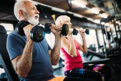 Fit senior sporty couple working out together at gym. Fit mature sporty couple working out to stay healthy royalty free stock photos