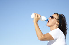Fit mature woman drinking water after exercise. An attractive looking mature woman is drinking bottled water after exercise, with ocean and spotless blue sky as Royalty Free Stock Photography