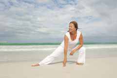 Fit mature woman exercising beach  Stock Image