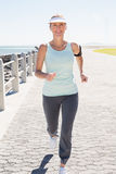 Fit mature woman jogging on the pier. On a sunny day Stock Photos