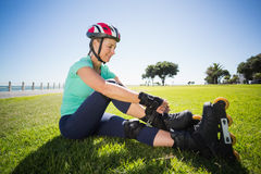 Fit mature woman tying her roller blades on the grass Stock Images