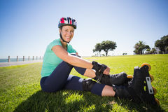 Fit mature woman tying her roller blades on the grass. On a sunny day royalty free stock photography