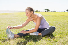 Fit mature woman warming up on the grass Royalty Free Stock Images