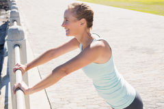 Fit mature woman warming up on the pier. On a sunny day Royalty Free Stock Images