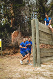 Fit men climbing a wooden wall during obstacle course Stock Images