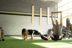 Man and woman training in gym together. Fit men and fit women training in gym together Stock Photography