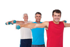 Fit men lifting dumbbells together Royalty Free Stock Image