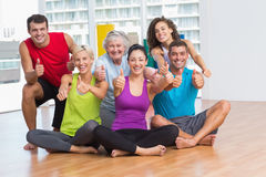 Fit men and women gesturing thumbs up in fitness studio. Full length portrait of fit men and women gesturing thumbs up in fitness studio Royalty Free Stock Photo