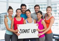 Fit men and women holding placard with start up text in fitness studio Stock Photography