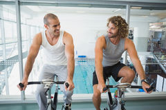 Fit men working on exercise bikes at gym Royalty Free Stock Photography