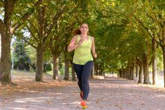 Fit middle-aged woman jogging through a park royalty free stock photo