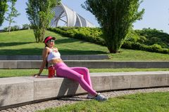 Fit middle-aged woman resting after training in park Royalty Free Stock Photography